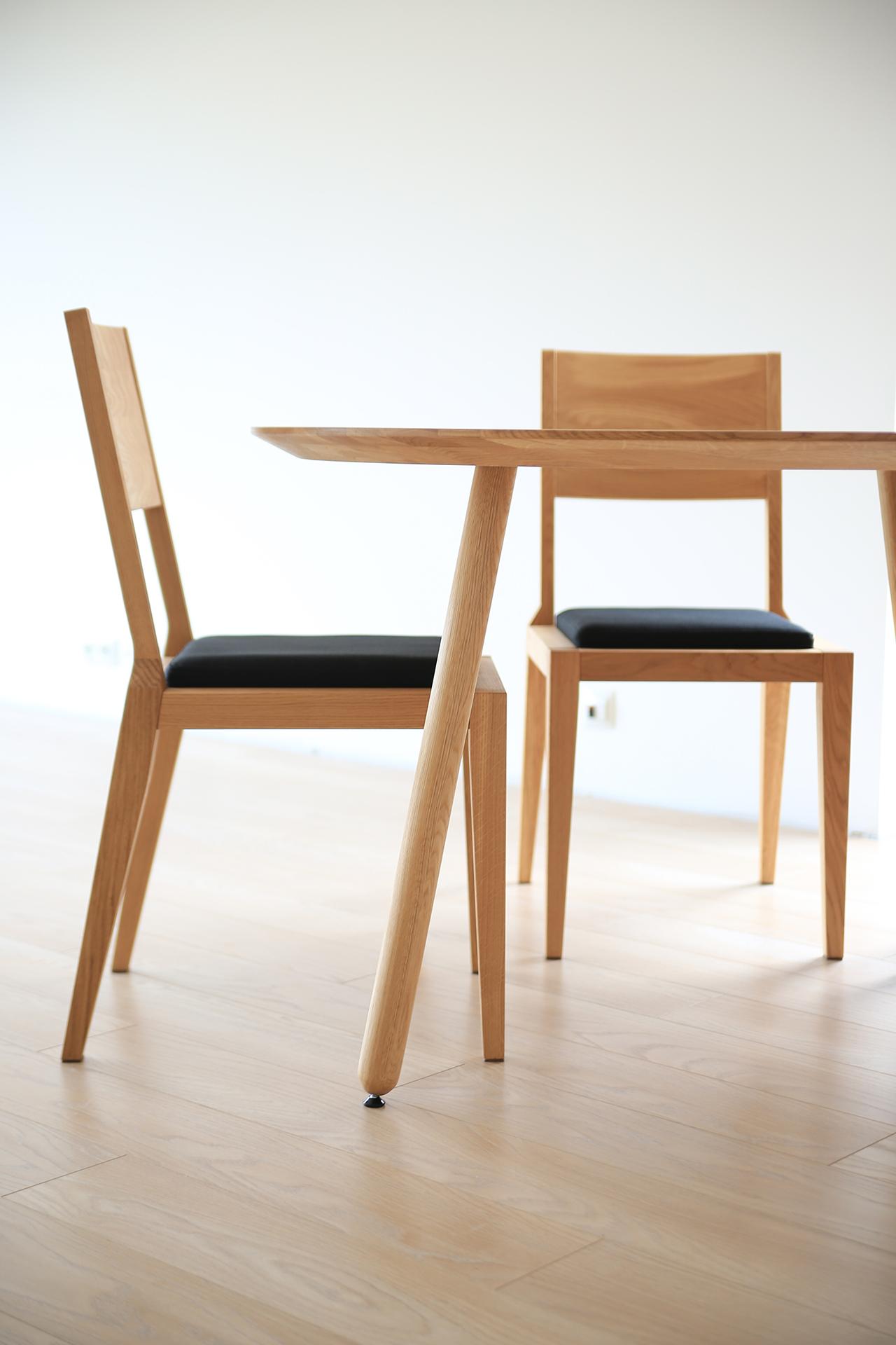 Stół okrągły OX i tapicerowane krzesła AVANGARDE firmy MILONI